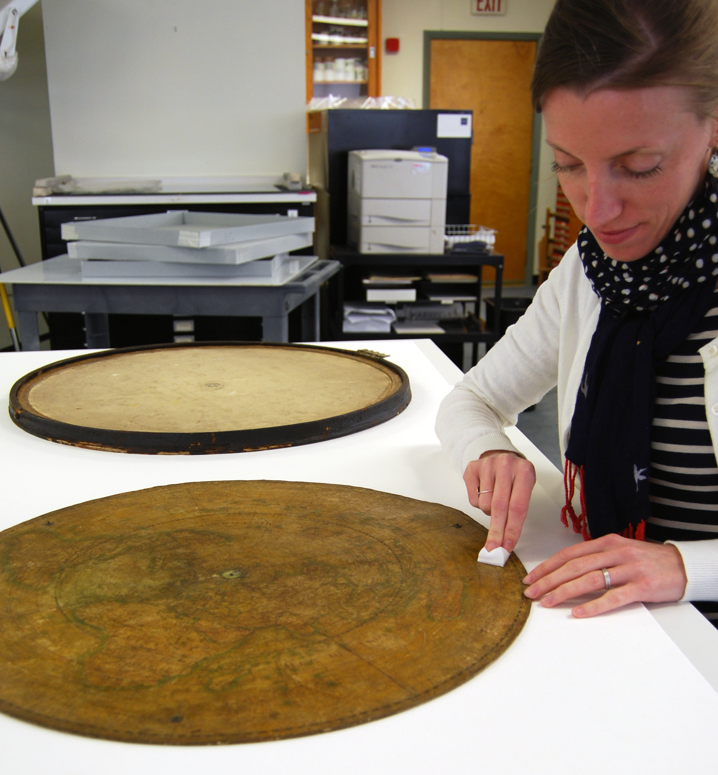 Conservator cleaning the map with a soft sponge