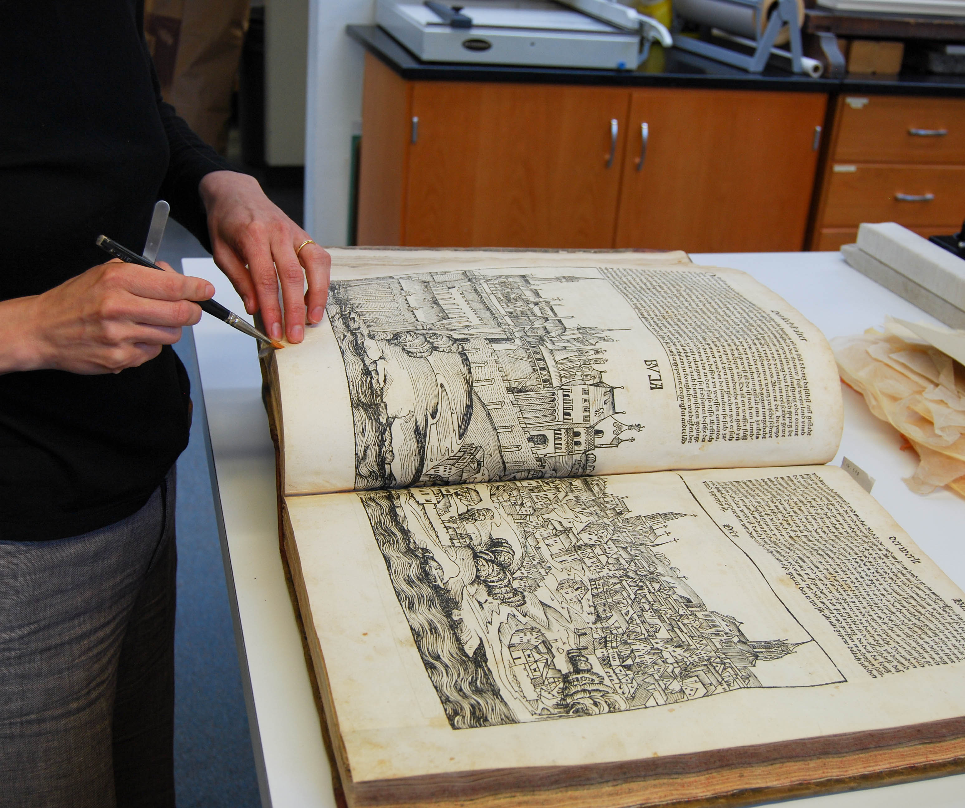 Conservator surface cleans manuscript pages