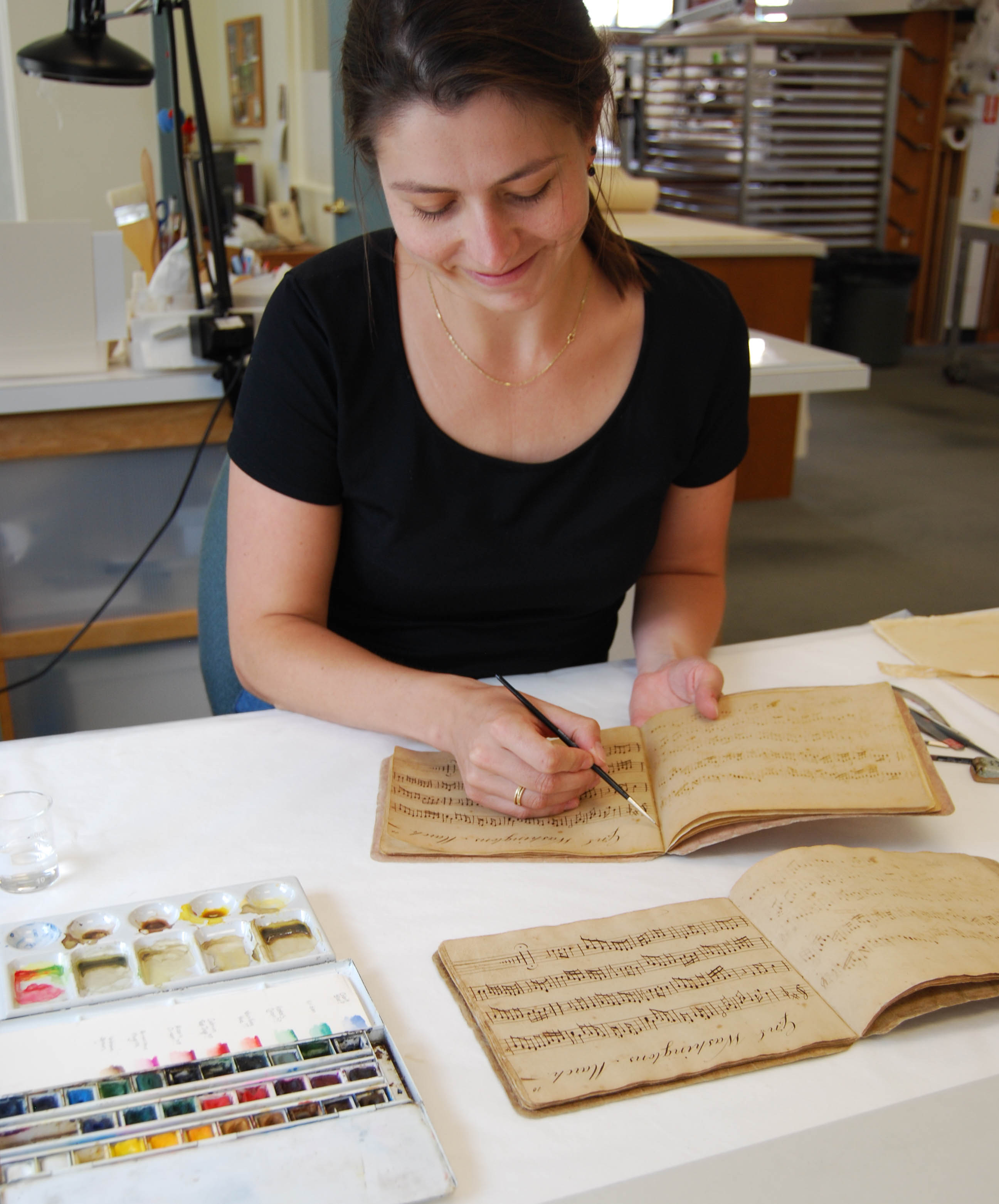 Conservator tones a page of a facsimile book
