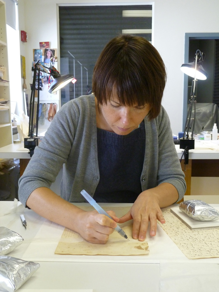 Conservator mends a tear in historic document