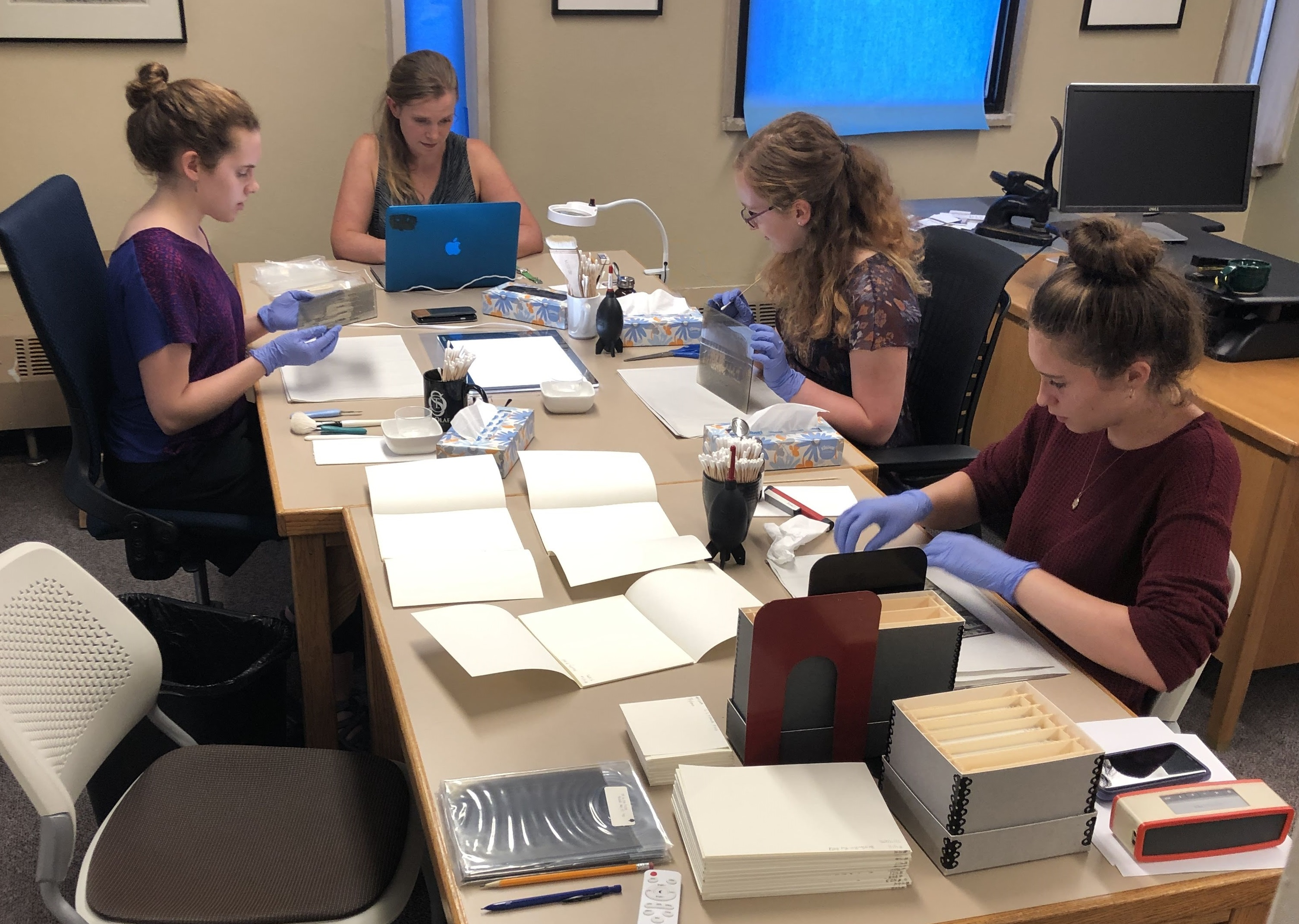 CCAHA staff and St. Olaf College library staff working together on glas plate negative treatment during a 2018 site visit.