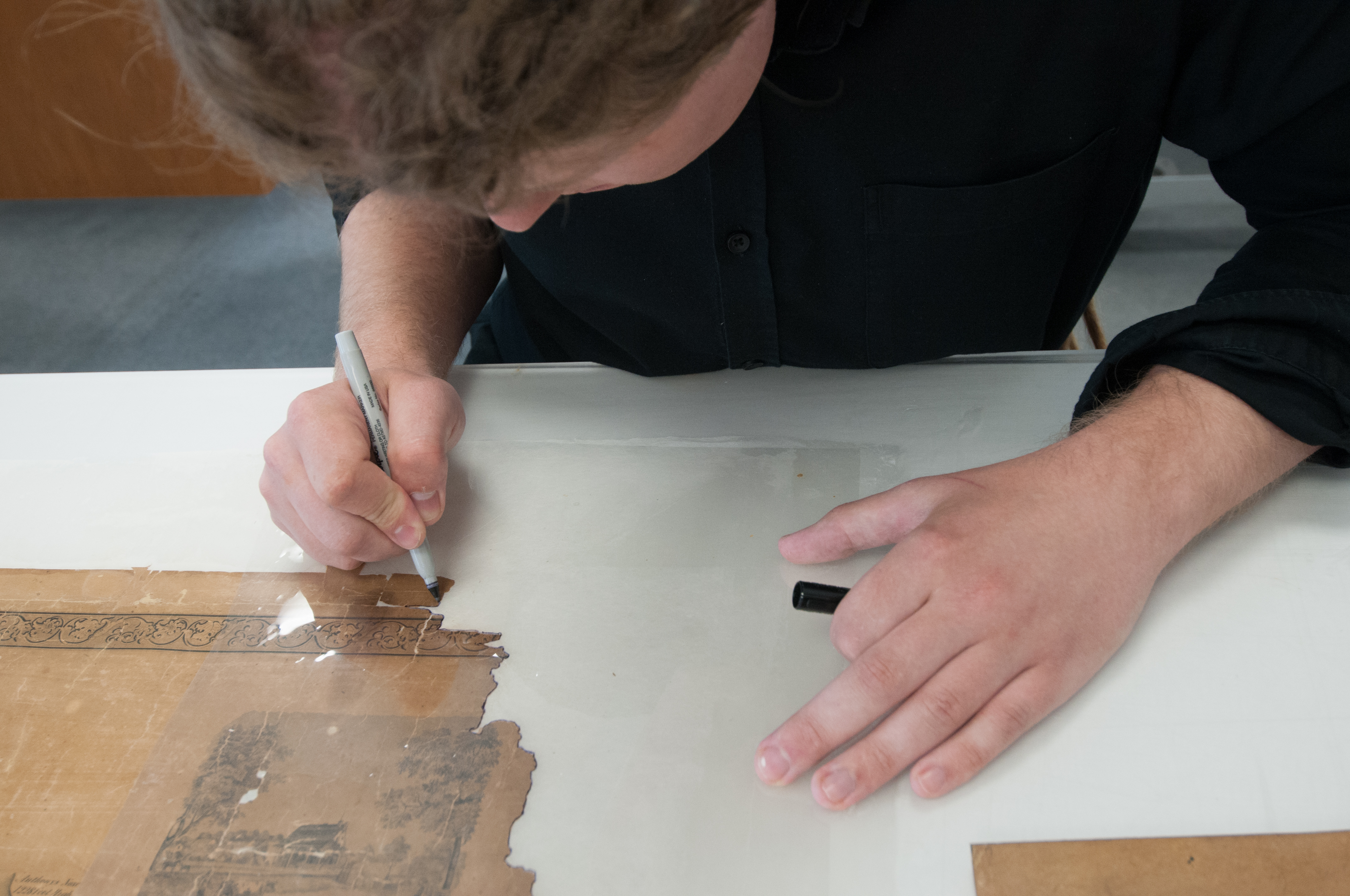 Paper Conservation Fellow Benjamin Kirschner treating a map's corner