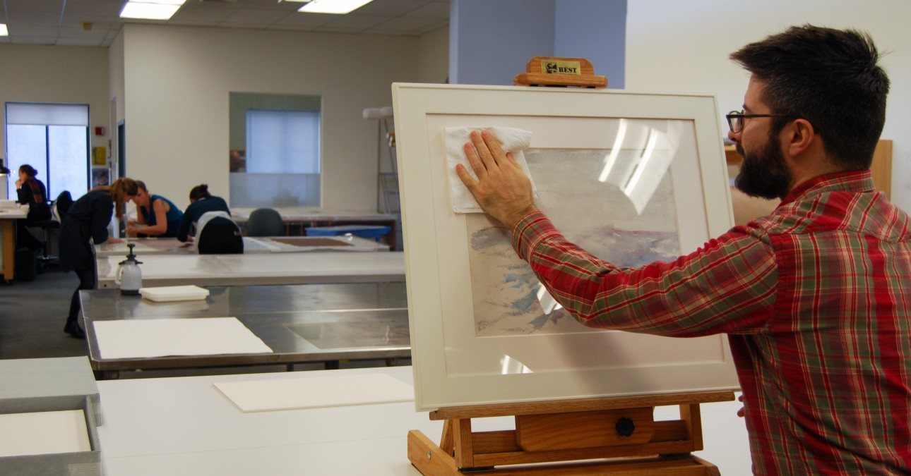 Man cleans glazing of framed watercolor