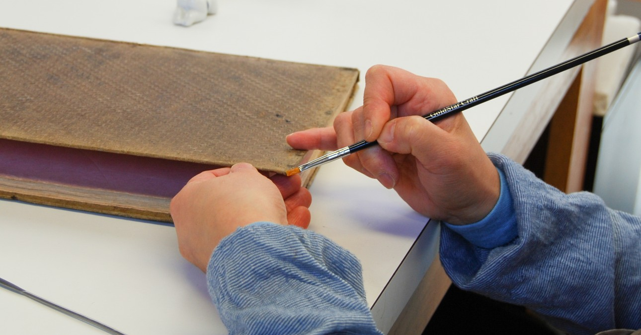 Conservator consolidates delaminating book cover edge