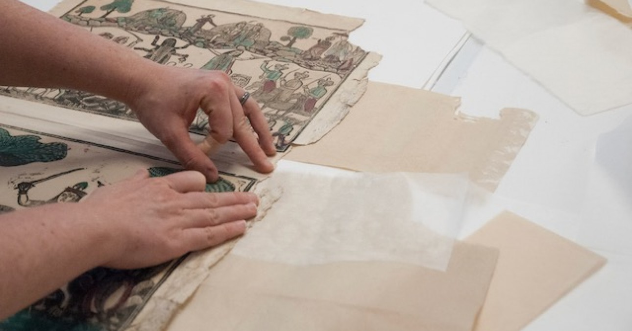Senior Paper Conservator Heather Hendry examines a variety of paper options to fill a losses