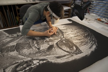 Applying wheat starch paste to a Chuck Close portrait