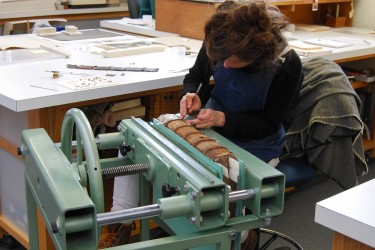 Conservator at a book press works on spine of manuscript
