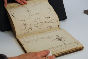 Surface cleaning a book with violin illustrations