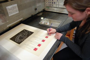 Conservator applies fixative to an area of red ink on a folio
