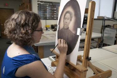 Conservator inpaints a crayon enlargement