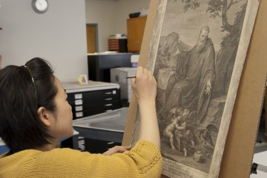 Conservator inpaints an etching