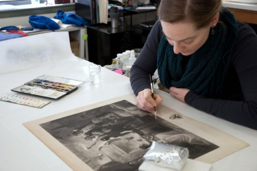 Conservator inpaints an engraving