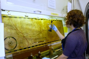 Conservator sprays solvent on map