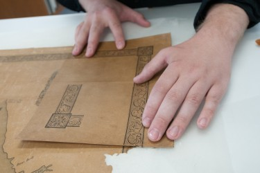 Paper Conservation Fellow Benjamin Kirschner aligns a map corner facsimile